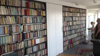 boekenkast, gerookt Eiken ,massief8 meter boekenkast, gerookt Eiken ,massief hout,amsterdam,boekenkast op maat,Boekenwand met kast in het midden die in zijn geheel naar buiten kan scharnieren,scharnierende kast op wielen